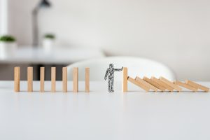 hand drawn shape of businessman stopping domino effect